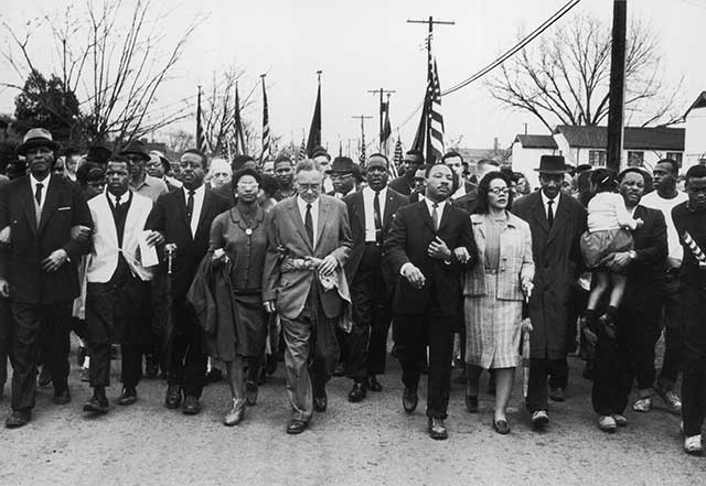 Martin Luther King and his wife Coretta Scott King lead a black voting rights march from Selma, Alabama, to the state capital in Montgomery in 1965. (Photo by William Lovelace/Express/Getty Images)