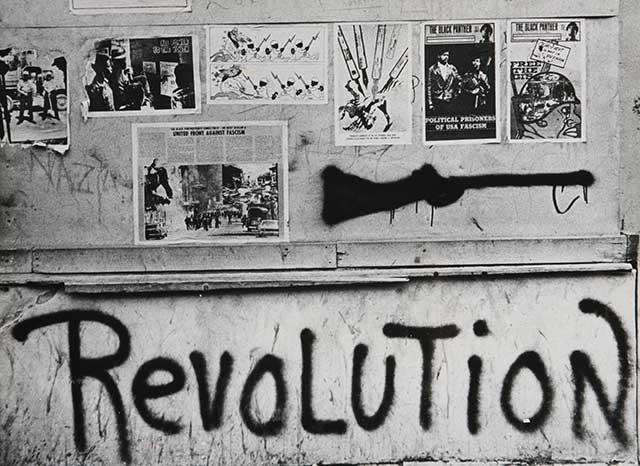 Amplified by the Black Panthers, whose posters adorn a Baltimore wall in 1970, that note of violent opposition to authority still echoes loudly in underclass culture today. (ULLSTEIN BILD / GRANGER, NYC — ALL RIGHTS RESERVED.)