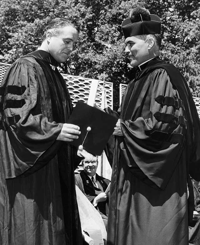 Then–Notre Dame president Rev. Theodore Hesburgh (right), shown here giving an honorary degree to Sargent Shriver in 1961, gathered together a group of Catholic academic leaders in Land O' Lakes, Wisconsin, to declare independence from Church authority. (