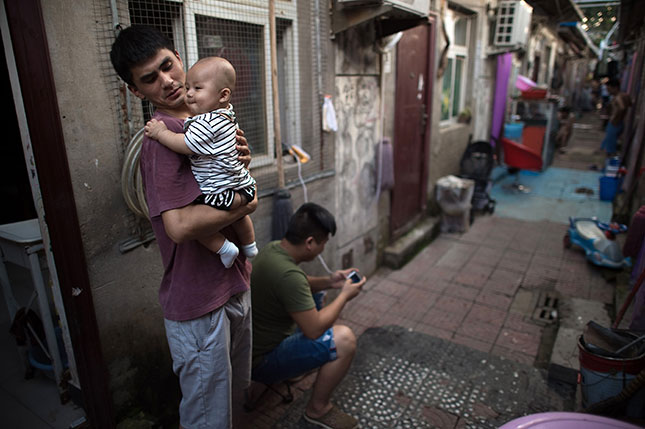 The rapid migration from China's countryside to its cities has created neighborhoods of intense poverty, often with several people occupying single rooms. (NICOLAS ASFOURI/AFP/GETTY IMAGES)