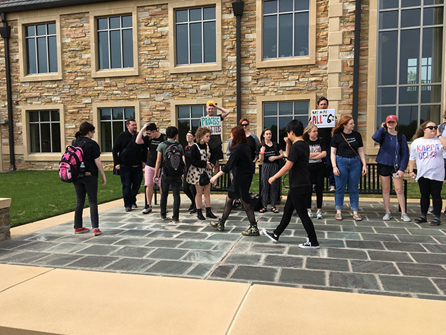 Students (wearing black, in mourning for the liberal arts) assemble for a peaceful protest at Collins Hall, the central administration building. (Photo: Courtesy of author)