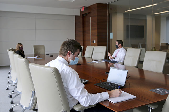 Employees wear protective masks at a socially distanced office meeting. (DYLAN HOLLINGSWORTH/BLOOMBERG/GETTY IMAGES)