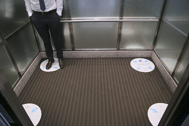 An employee stands on a social-distance marker in an office elevator. (DYLAN HOLLINGSWORTH/BLOOMBERG/GETTY IMAGES)