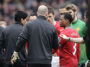Liverpool's Luis Suarez (left) refuses to shake the hand of Manchester United's Patrice Evra, who had accused him of racial taunts.