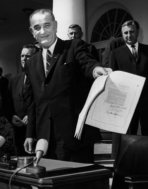 LBJ brandishes the freshly signed War on Poverty bill in 1964.