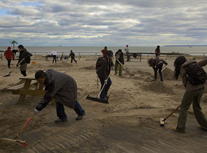 Volunteers sweep sand from the storm-battered Coney Island boardwalk.