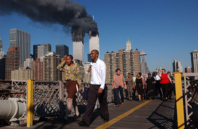 People flee Manhattan over the Brooklyn Bridge as the World Trade Center burns on September 11, 2001. (SPENCER PLATT/GETTY IMAGES)