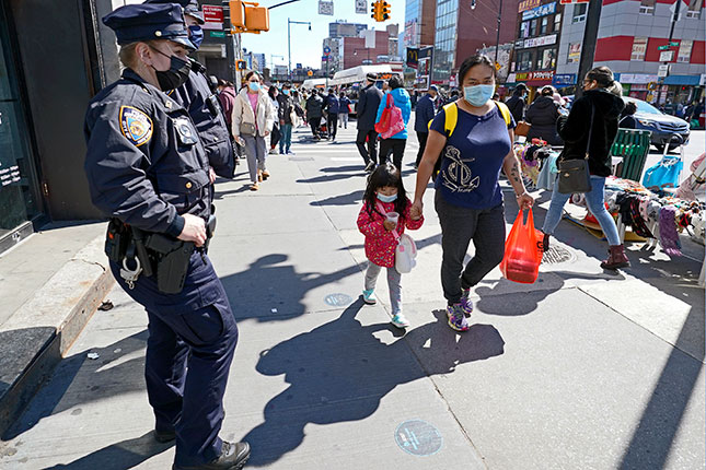 """Police patrol a shopping district in Queens, 2021: Wilson argued that """"the essence of the police role in maintaining order is to reinforce the informal control mechanisms of the community itself."""" (KATHY WILLENS/AP PHOTO)"""
