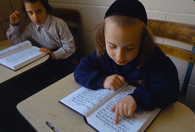 A pupil studying a prayer book (ANDREW LICHTENSTEIN/CORBIS/GETTY IMAGES)